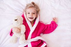 Funny kid girl in room. Happy kid girl 3-4 year old holding teddy bear lying in bed wearing bathrobe closeup. Looking at camera. Good morning. Top view stock photos