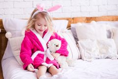 Funny kid girl in room. Hapy kid girl 3-4 year old playing with teddy bear wearing bathrobe sitting in room. Good morning stock photo