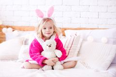 Funny kid girl in room. Smiling kid girl 4-5 year old holding teddy bear sitting in bed close up. Good morning stock images