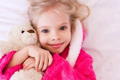 Funny kid girl in room. Smiling kid girl 4-5 year old holding teddy bear lying in bed. Looking at camera. Childhood royalty free stock photo