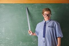 Funny kid girl at school teacher costume. Funny kid girl with teacher costume in green blackboard with school ruller royalty free stock image