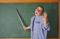 Funny kid girl at school teacher costume. Funny kid girl with teacher costume in green blackboard with school ruller royalty free stock photo
