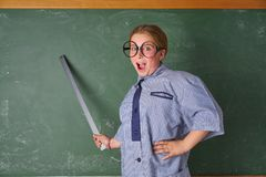 Funny kid girl at school teacher costume. Funny kid girl with teacher costume in green blackboard with school ruller stock image