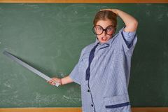 Funny kid girl at school teacher costume. Funny kid girl with teacher costume in green blackboard with school ruller stock photo
