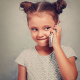 Funny kid girl talking on mobile phone with happy smile on blue. Background with empty copy space. Toned closeup portrait Stock Image