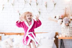 Funny kid girl in room. Funny kid girl 4-5 year old wearing bathrobe jumping in bed close up. Looking at camera. Childhood stock photos
