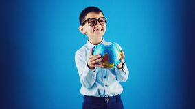 Happy funny kid with globe on a blue background.