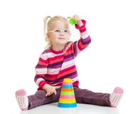Funny kid in glasses playing colorful pyramid toy Royalty Free Stock Images
