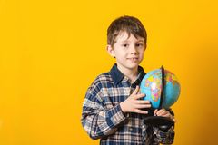 Funny kid with globe, isolated on yellow. Back to school concept. Educational globe. Curious child holding earth globe map in his royalty free stock photos