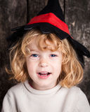 Funny kid in hand of witch. Happy laughing kid in hat of witch. Halloween concept Stock Photo