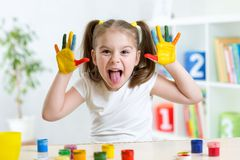 Funny kid with hands painted in colorful paint Stock Photos