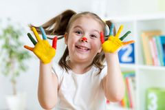 Funny kid with hands painted in colorful paint Royalty Free Stock Photos
