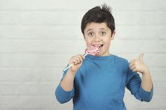 Funny kid with lollipop. On brick background stock photos
