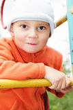 Funny kid in orange on climbing staircase Stock Photo