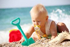 Funny kid playing  on the beach Stock Photos