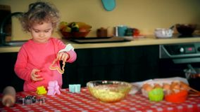Funny kid playing with colorful cookie forms. Girl she looks curious. Static closeup shot. 4K UHD stock video