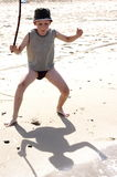 Funny kid playing with stick on a beach sand Royalty Free Stock Photos