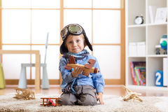 Funny kid playing with toy airplanes at home. Travel and dream concept Stock Images