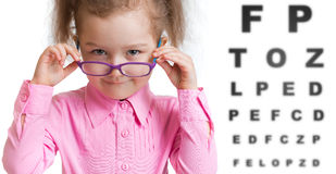 Funny kid putting on spectacles in ophthalmologist stock images
