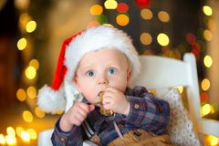 Funny kid in santa claus hat. A small funny kid with a surprised look sits on the chair with a gift in his hands, a set of bright festive lights in the Stock Images