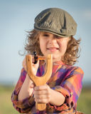 Funny kid shooting wooden slingshot Stock Photography