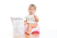 Funny kid sitting on chamberpot with newspaper. Funny child girl sitting on chamberpot with eyeglasses and newspaper royalty free stock photography