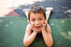 Funny kid sitting on ground Stock Image