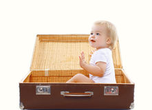 Funny kid sitting in the travel suitcase having fun. And playing Stock Images