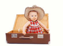 Funny kid in a summer hat. Is sitting on a suitcase Stock Photos
