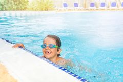 Funny kid swimming in the pool with goggles Stock Photography