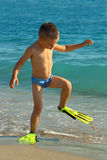 Funny kid walking the beach wearing flippers. Funny boy kid walking the beach wearing flippers Stock Image