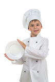 Funny kid wearing chef uniform holding plate in his hands on white background. Stock Image