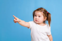Funny kid in white T-shirt on blue background. Little pretty girl isolated on blue background. Copy space for text. Stock Photo