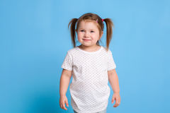 Funny kid in white T-shirt on blue background. Little pretty girl isolated on blue background. Copy space for text. Sale, holidays, birthday party concept royalty free stock images