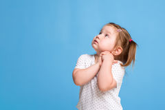 Funny kid in white T-shirt on blue background. Little pretty girl isolated on blue background. Copy space for text. Royalty Free Stock Photography