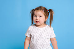 Funny kid in white T-shirt on blue background. Little pretty girl isolated on blue background. Copy space for text. Stock Photos