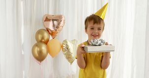 Funny kid in yellow t-shirt holds paper present box closeup