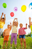 Funny kids with balloons in the air. In green field royalty free stock photo