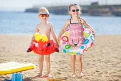 Funny kids with colorful buoys on the beach Stock Images