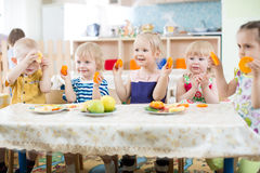 Funny kids eating fruits in kindergarten or day care centre. Funny kids eating fruits in day care centre royalty free stock images