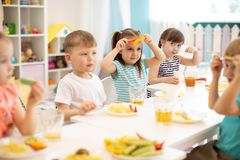 Funny kids eating vegetables in kindergarten royalty free stock photo