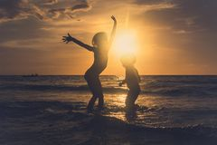 Funny kids. Dancing on the tropical beach at sunset royalty free stock images