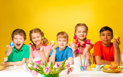 Funny kids holding coloured Easter eggs at table Royalty Free Stock Photos