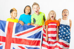 Funny kids holding flag Great Britain and american national flag. Funny kids holding flag of Great Britain and american national flag. Group of school children Royalty Free Stock Photography