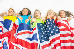 Funny kids holding flag Great Britain and american national flag. Funny kids holding flag of Great Britain and american national flag. They shows thumbs down Royalty Free Stock Images