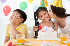 Funny kids. Image of a boy taking offence while his mother kissing his b-day sister on the foreground Stock Photo
