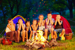 Funny kids with painted faces on hands sitting around camp fire Royalty Free Stock Photos
