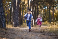Funny kids playing in the park. Funny children are playing in the park. A boy and a girl. Carefree childhood Stock Images