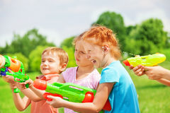 Funny kids playing with water guns. Funny kids playing on a meadow with water guns Royalty Free Stock Image