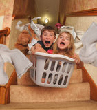 Funny Kids Riding In Laundry Basket Downstairs. Two young children are riding in a laundry basket down the house stairs with socks flying for a parenting royalty free stock image